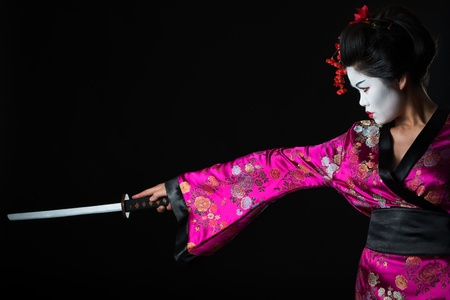 Portrait of geisha warrior with sword isolated on black photo