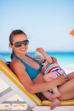Mother laying on sunbed and holding baby drinking water photo