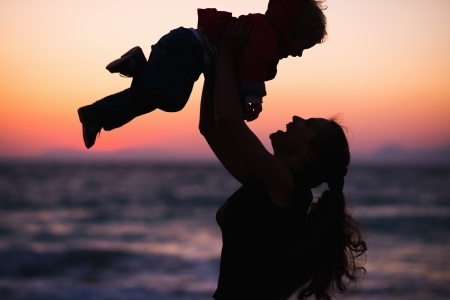 Silhouette of mother throwing baby up on sunset photo