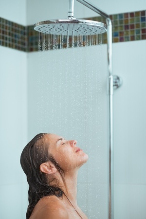 douche: Woman with long hair taking shower under water jet Stock Photo
