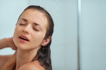 personas tomando agua: Retrato de mujer relajada tomando ducha