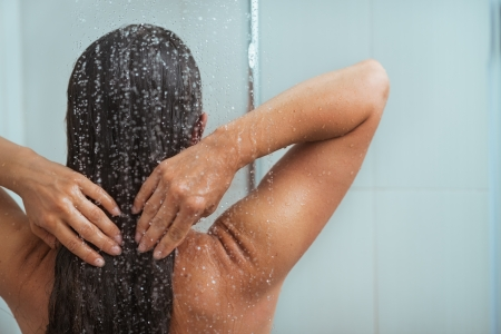 Woman washing long hair in shower under water jet photo