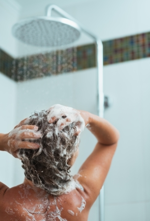 Woman applying shampoo in shower. Rear view photo