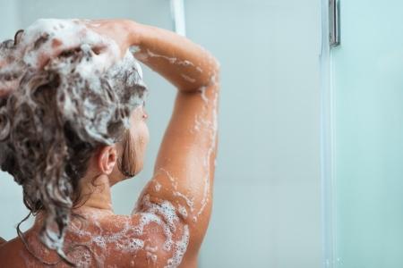 aseo personal: Mujer de aplicar el champ� en la ducha. Vista trasera