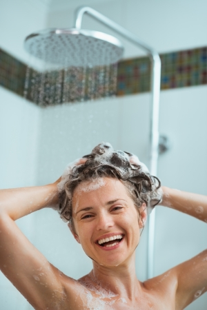 Happy woman applying shampoo in shower photo