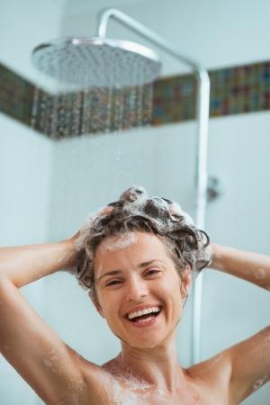 Happy woman applying shampoo in shower Stock Photo - 14634452