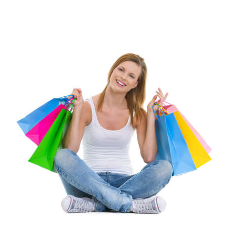 Full length portrait of smiling teenage girl sitting with shopping bags photo