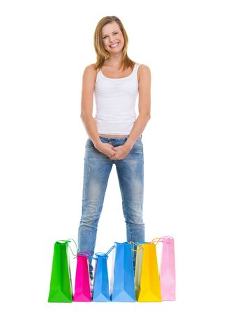 Full length portrait of smiling teenage girl standing among shopping bags photo