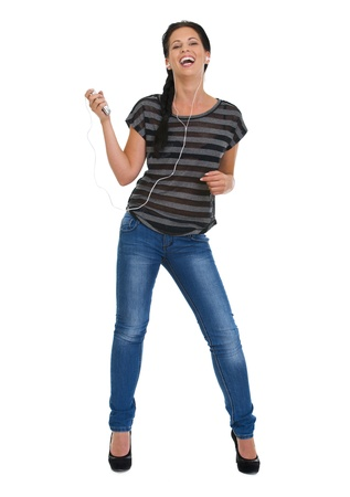 Full length portrait of happy girl with headphones dancing photo