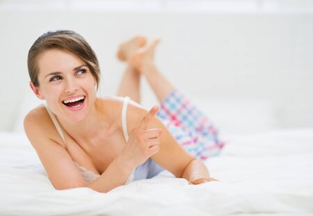 sleepwear: Happy woman laying on bed and pointing on copy space
