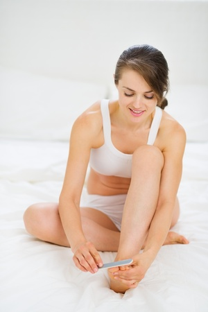 Woman sitting on bed and taking care of nails on feet photo