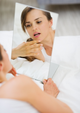 check room: Young woman laying on bed and checking face in mirror Stock Photo