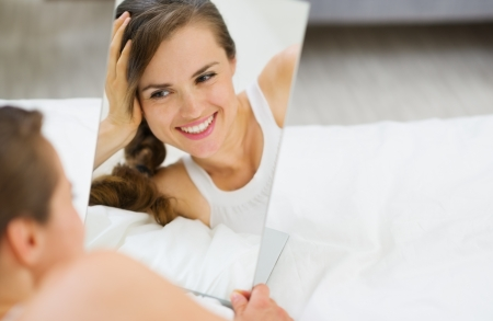 Happy young woman laying on bed and looking on mirror photo