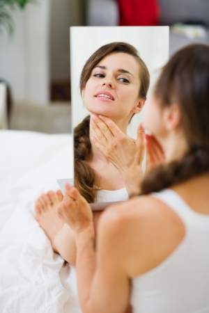 looking in mirror: Happy young woman sitting on bed and looking on mirror Stock Photo