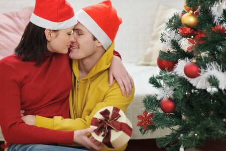 Romantic young couple with gift kissing near Christmas tree photo