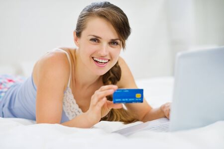 Happy young woman laying on bed with credit card and laptop photo