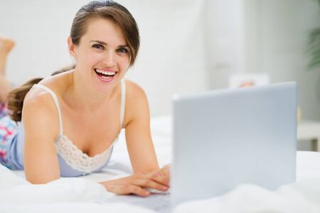 Smiling young woman laying on bed and using laptop Stock Photo - 14768092