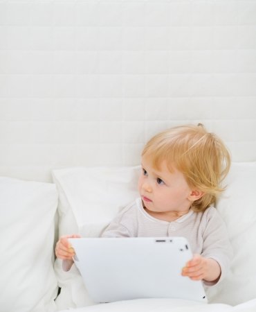 Modern baby with tablet PC photo
