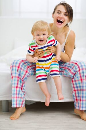 Portrait of happy young mother with baby in bedroom Stock Photo - 14768025