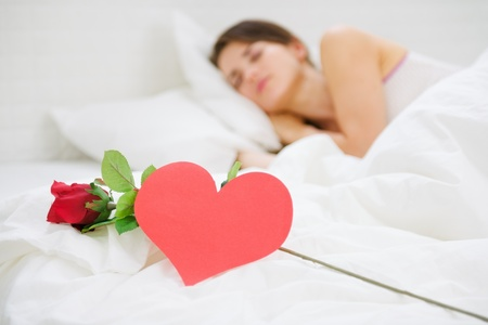 Closeup on red rose and heart shaped postcard near sleeping woman photo