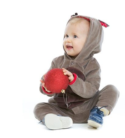 Smiling baby with Christmas ball looking on copy space photo