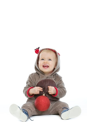 Smiling baby with Christmas ball looking up on copy space photo