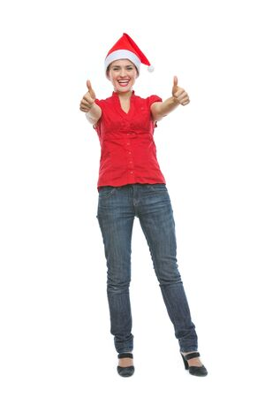 Full length portrait of smiling young woman in Christmas hat showing thumbs up photo