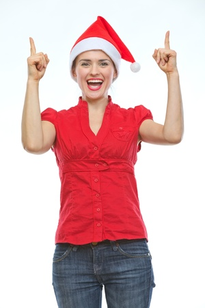 Smiling young woman in Christmas hat pointing up Stock Photo - 14768188