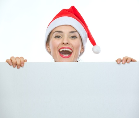 Happy woman in Christmas hat looking out from blank billboard Stock Photo - 14768191