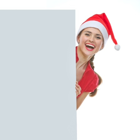 Smiling woman in Christmas hat looking out from blank billboard Stock Photo - 14768180