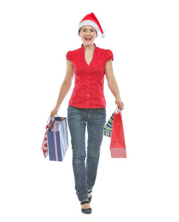 Happy woman in Christmas hat with shopping bags making step forward Stock Photo - 14768143