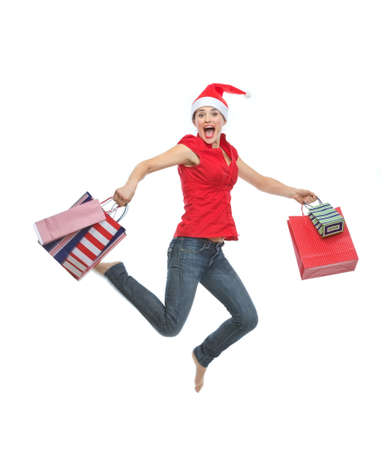 Happy woman in Christmas hat with shopping bags jumping photo