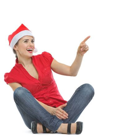Happy woman in Christmas hat sitting on floor and pointing on copy space Stock Photo - 14768181