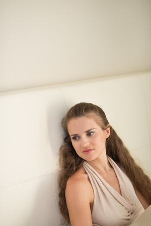 Portrait of thoughtful young woman sitting on couch Stock Photo - 14901608