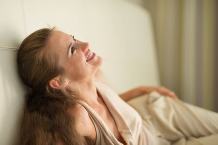 Portrait of laughing young woman laying on couch photo