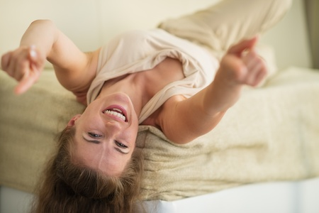 Laughing young woman laying on couch and pointing in camera photo