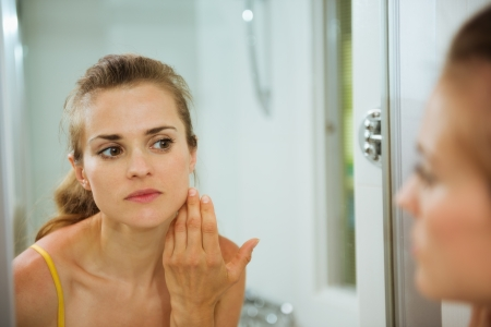 woman bath: Young woman checking her face in mirror in bathroom