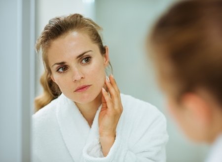 Young woman in bathrobe checking her face in mirror in bathroom photo