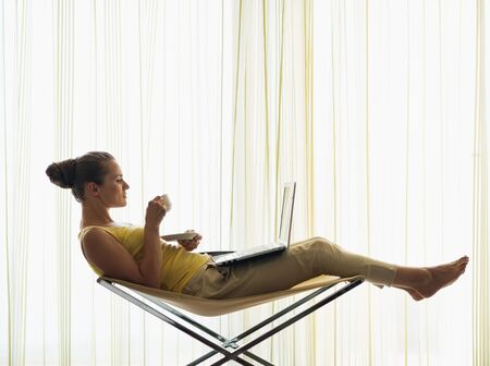 Young woman with coffee cup using laptop at home Stock Photo - 14901604