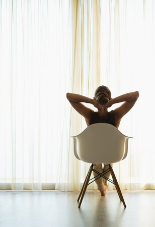 Woman sitting in front of window. Rear view Stock Photo - 14901609