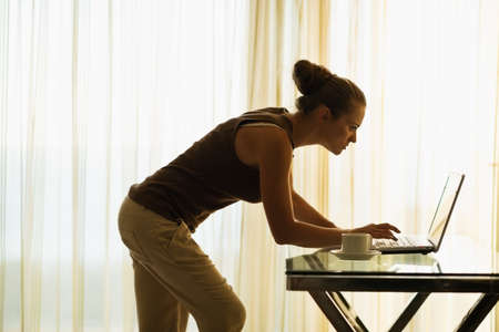 Young woman using laptop leaning against table Stock Photo - 14901600