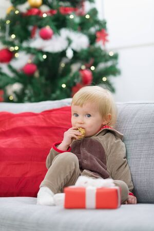 Baby in suit of Santa's little helper with Christmas gift eating cookie Stock Photo - 14917659