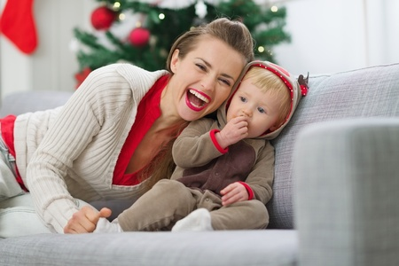 Smiling young mother and baby having fun time on Christmas Stock Photo