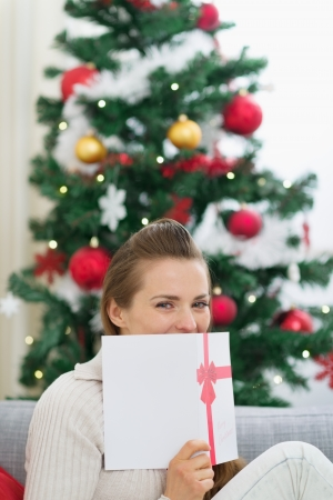 Female hiding behind Christmas postcard Stock Photo - 14901624