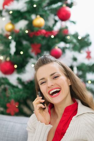 Happy young woman speaking mobile phone near Christmas tree Stock Photo - 14901652