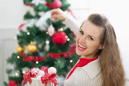 Happy young woman decorating Christmas tree Stock Photo - 14901649