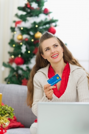 Woman with credit card thinking about Christmas presents Stock Photo - 14901636