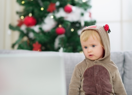 Thoughtful baby in deer suit near Christmas tree looking in laptop Stock Photo - 14902508
