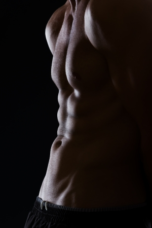 Closeup on muscular male torso with abdominal muscles on black photo