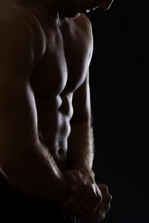 Closeup on man showing muscular body on black photo